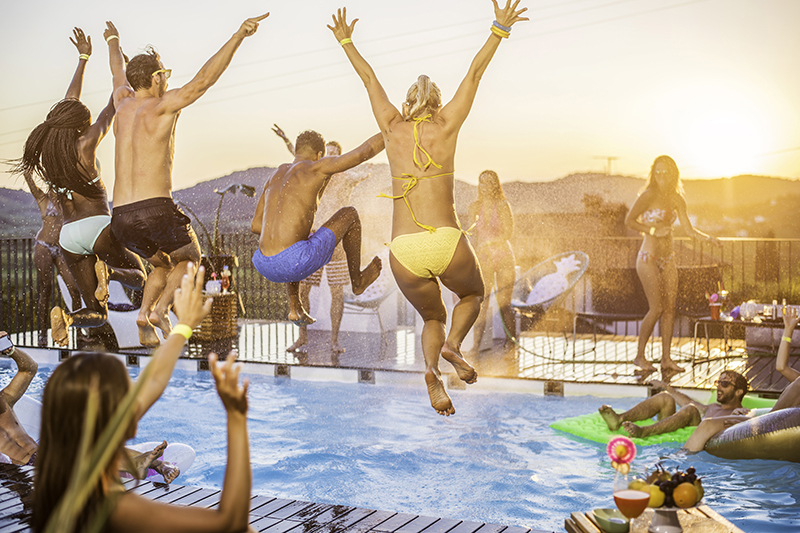 Young people in bikini and swimming shorts jumping in the pool on pool party, shot in maid-air.