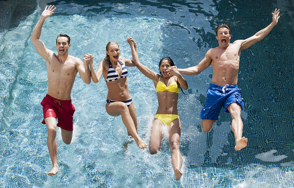 Four young people jumping into a swimming pool